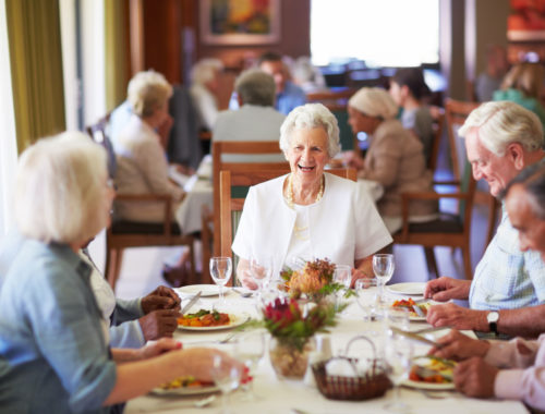 group of elderly people eating dinner together